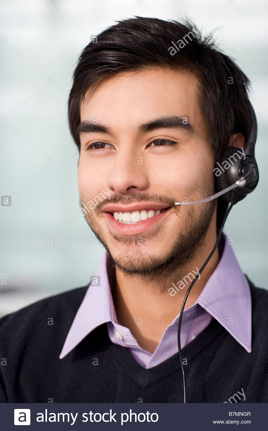 A dark haired male wearing a telesales headset - Stock Image