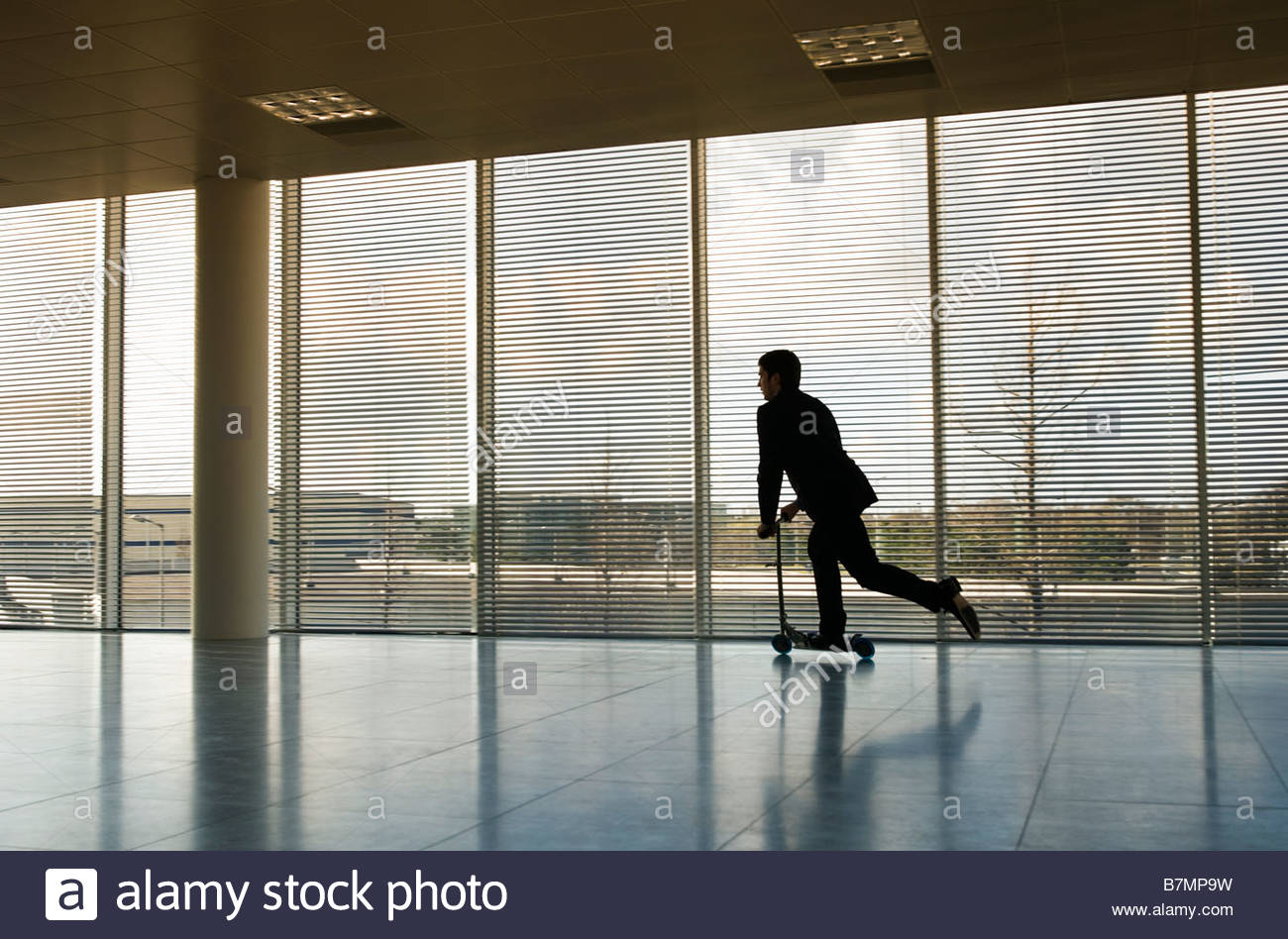 A businessman riding a scooter in an empty office - Stock Image