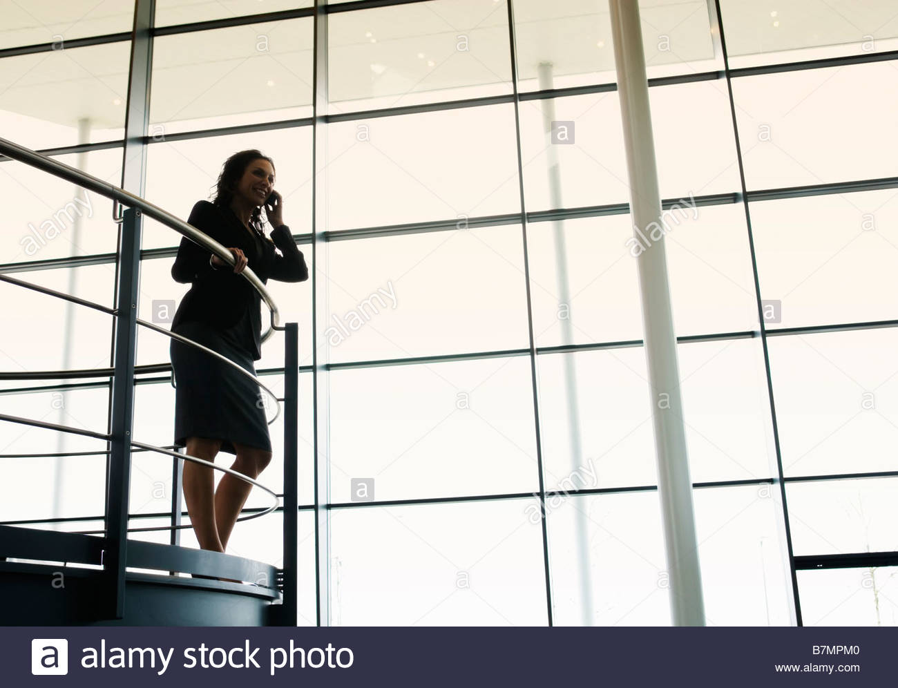 A businesswoman talking on a mobile phone in a modern office building Stock Photo