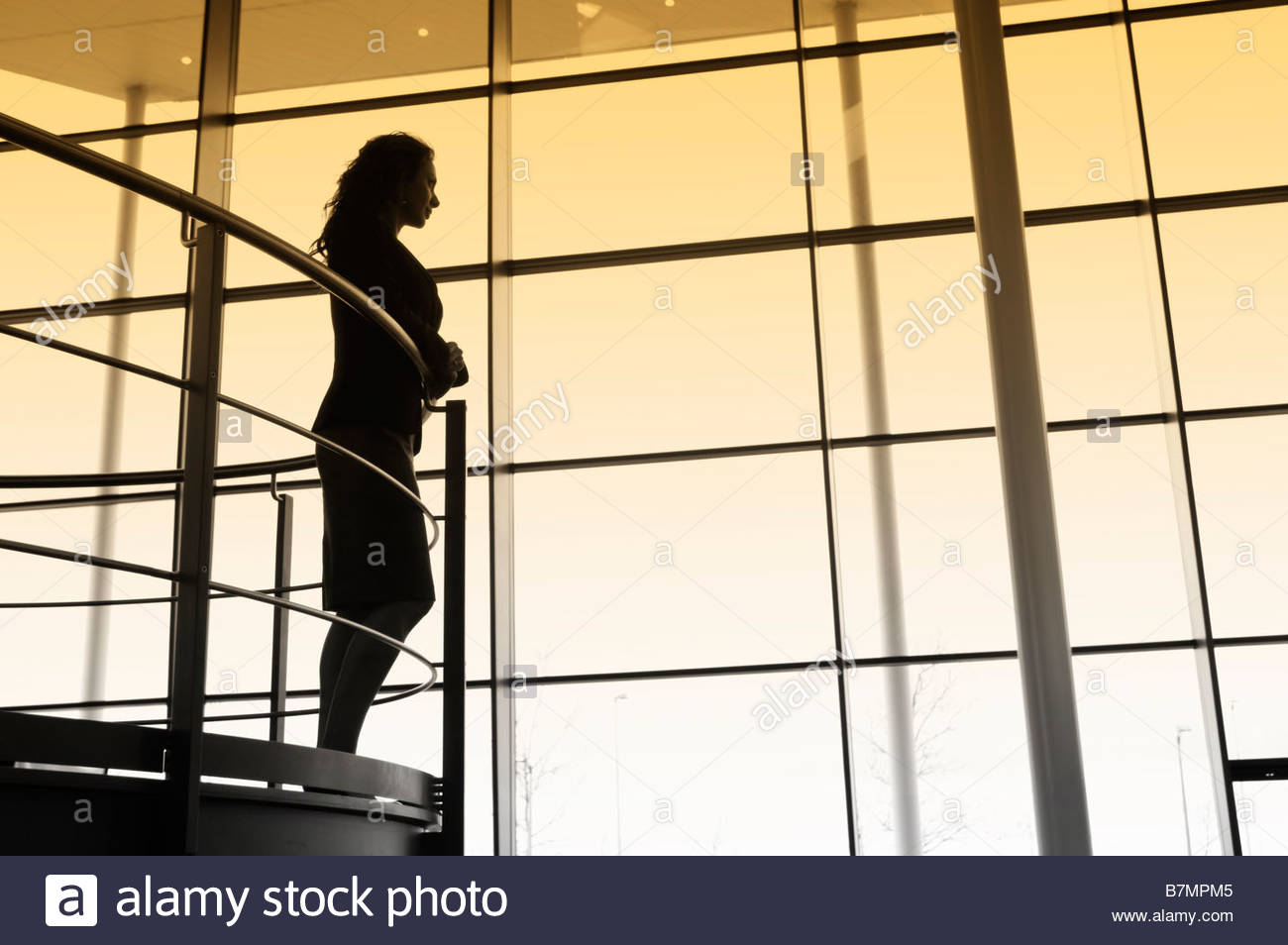 A businesswoman looking over balcony railings in a modern office building - Stock Image