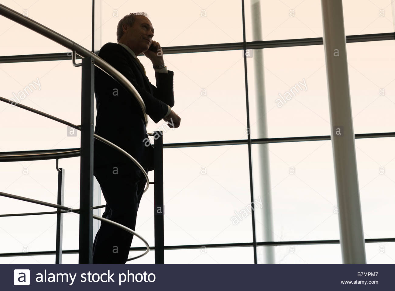 A businessman talking on a mobile phone in a modern office building Stock Photo