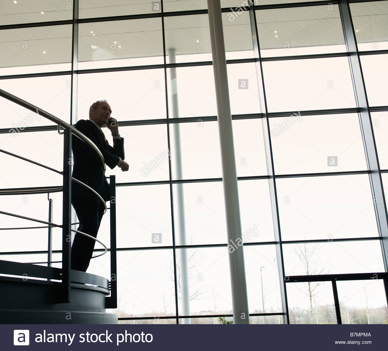 A businessman talking on a mobile phone in a modern office building - Stock Image