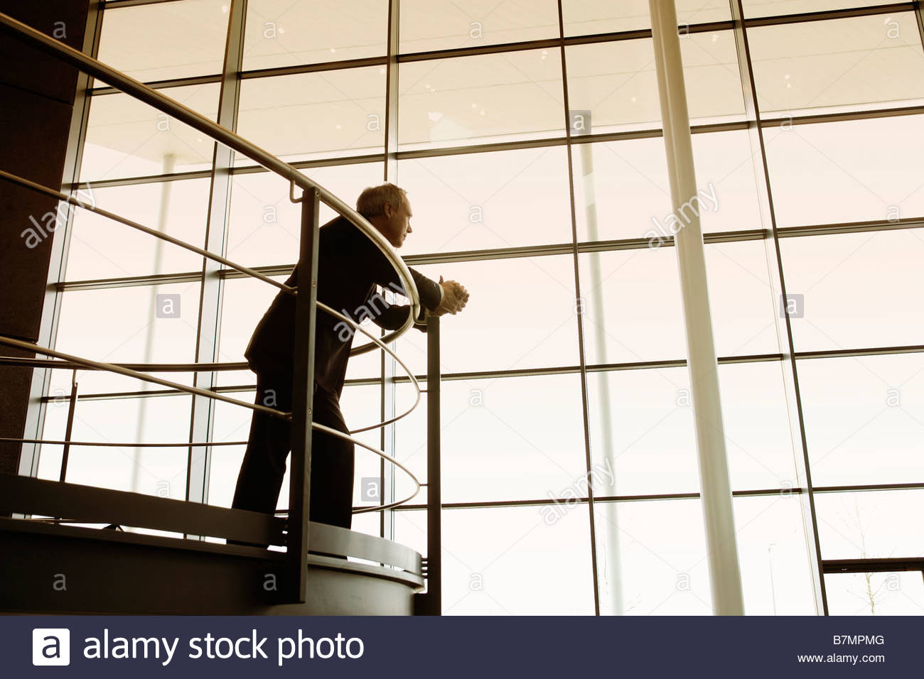 A businessman looking over balcony railings in a modern office building Stock Photo