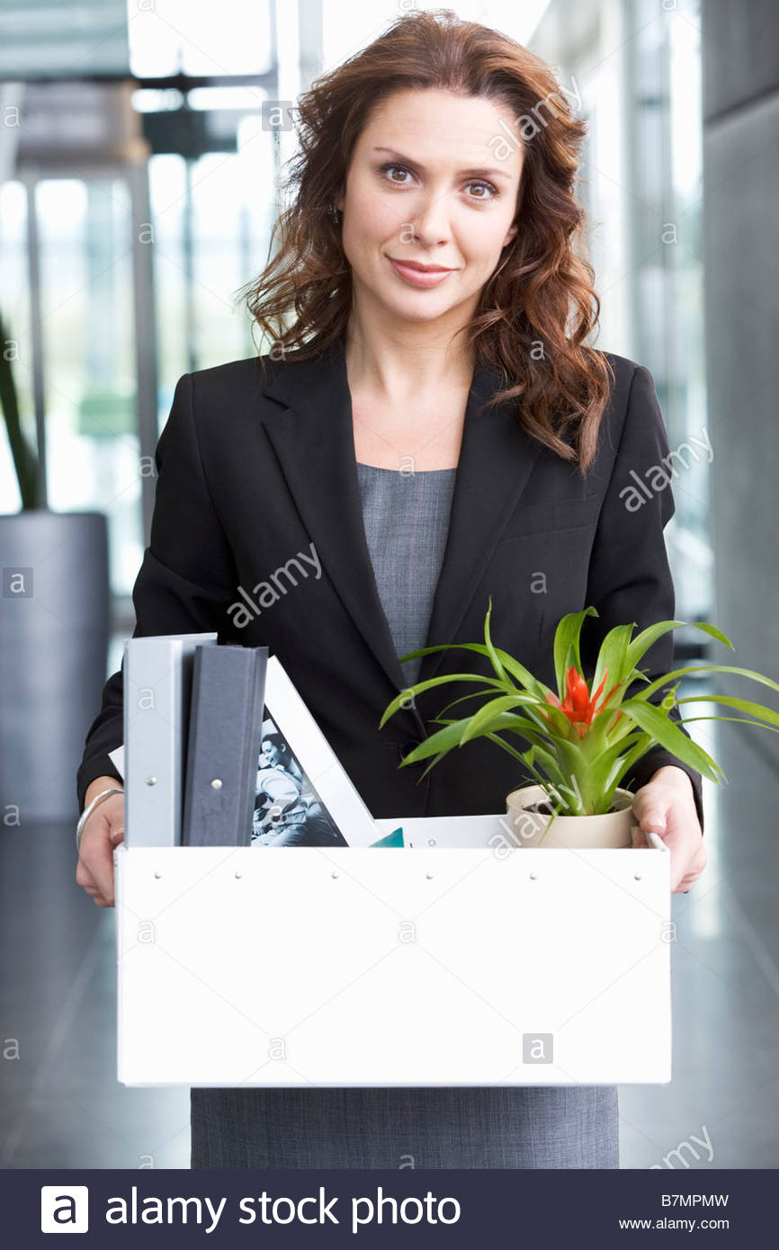A redundant businesswoman taking her belongings home in a box - Stock Image