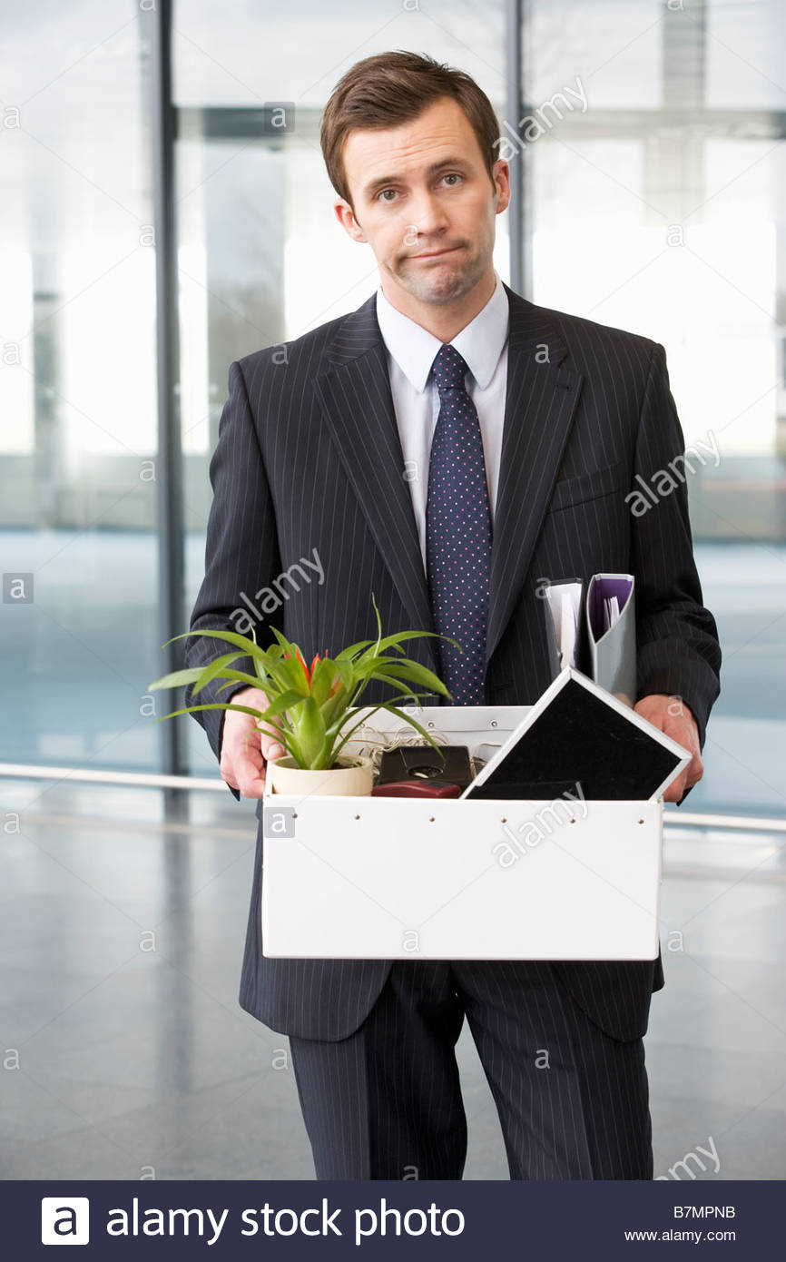 A redundant businessman taking his belongings home in a box - Stock Image