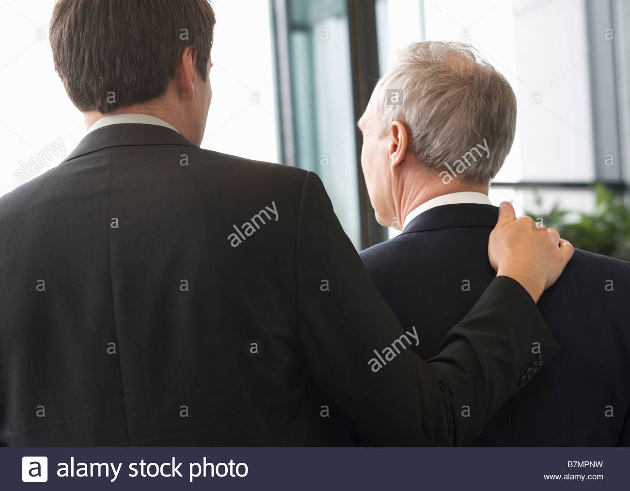 Two businessman leaving an office building - Stock Image