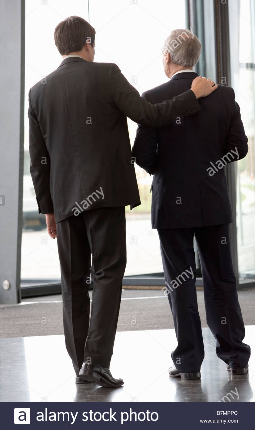 Two businessmen leaving an office building - Stock Image