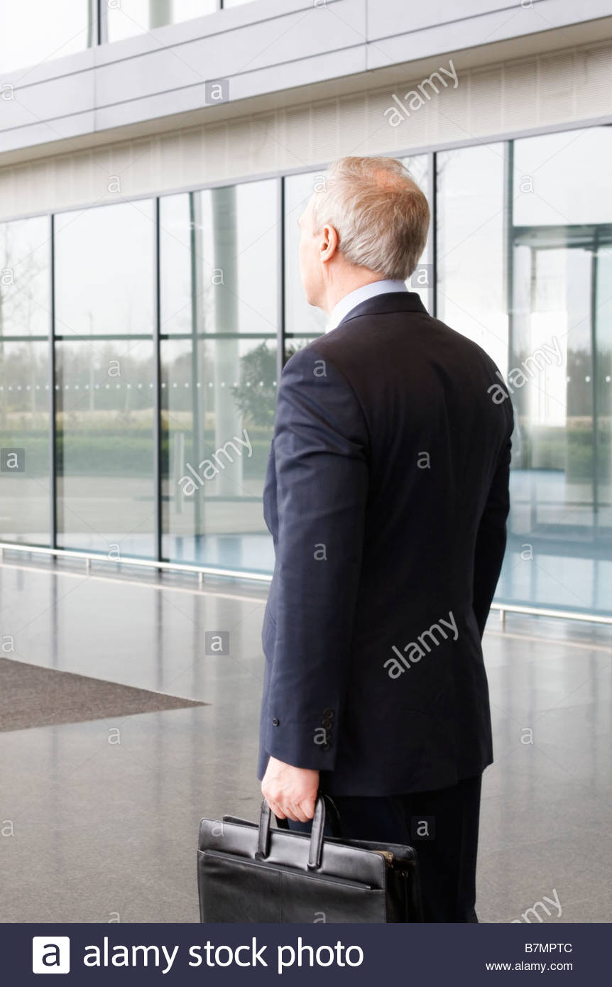 A businessman with a briefcase at a modern office building - Stock Image