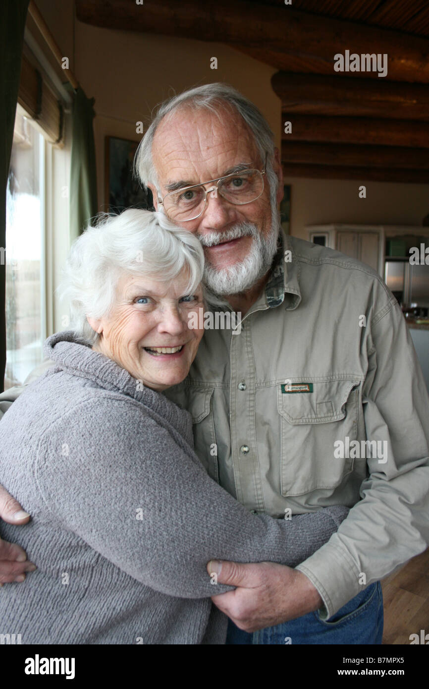 cute elderly married couple in seventies, embracing at home, smiling at camera - Stock Image