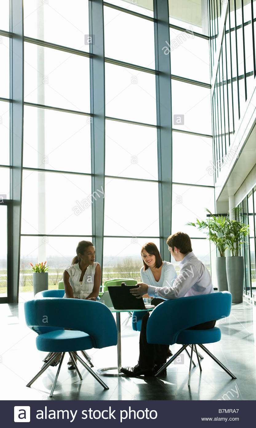 A group of friends or work colleagues sitting at a table having an informal meeting - Stock Image