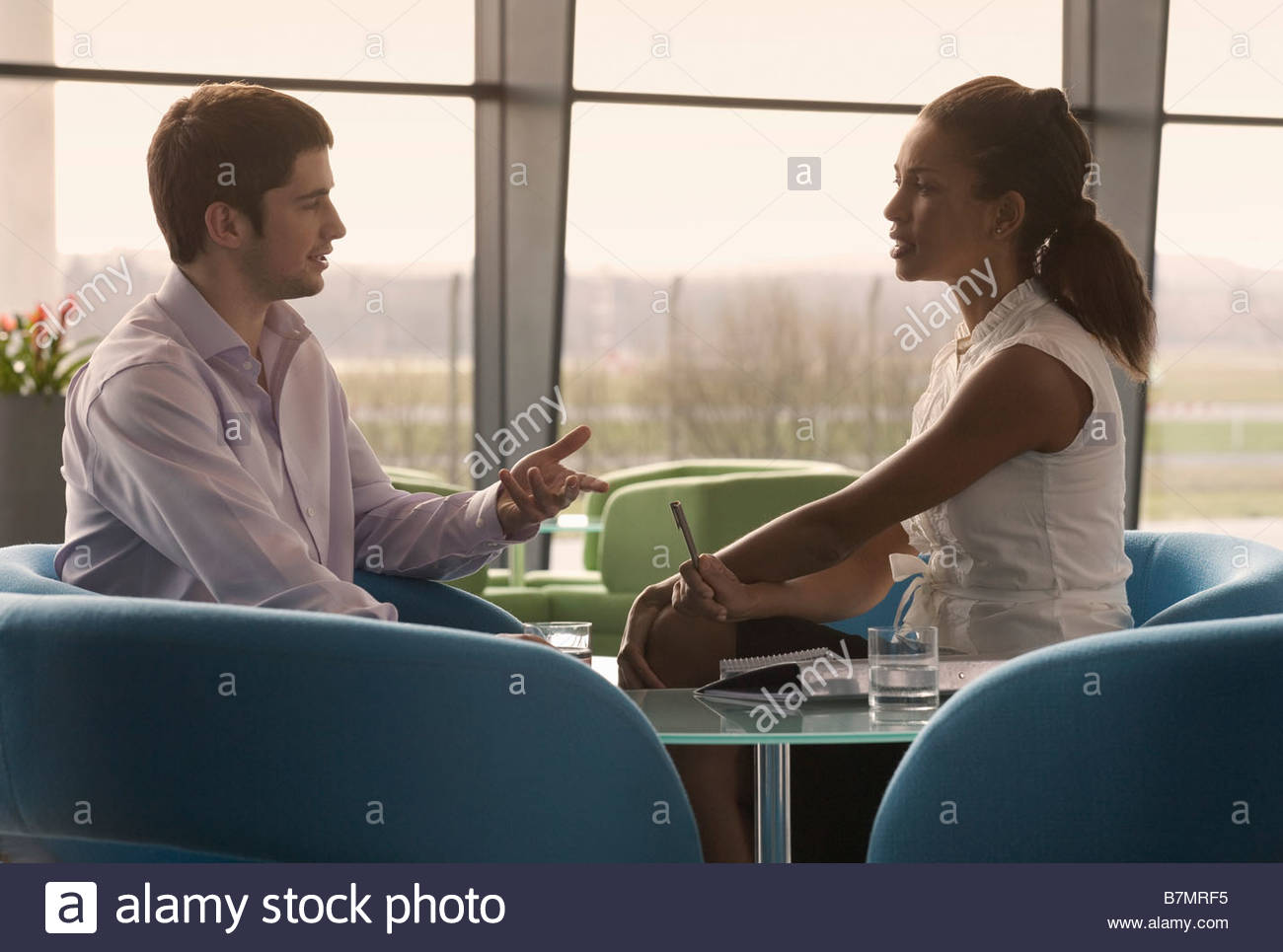 Two business colleagues sitting at a table, having a meeting - Stock Image