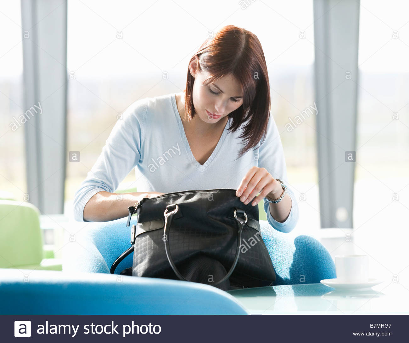 A woman sitting at a table, searching for an item in her handbag - Stock Image