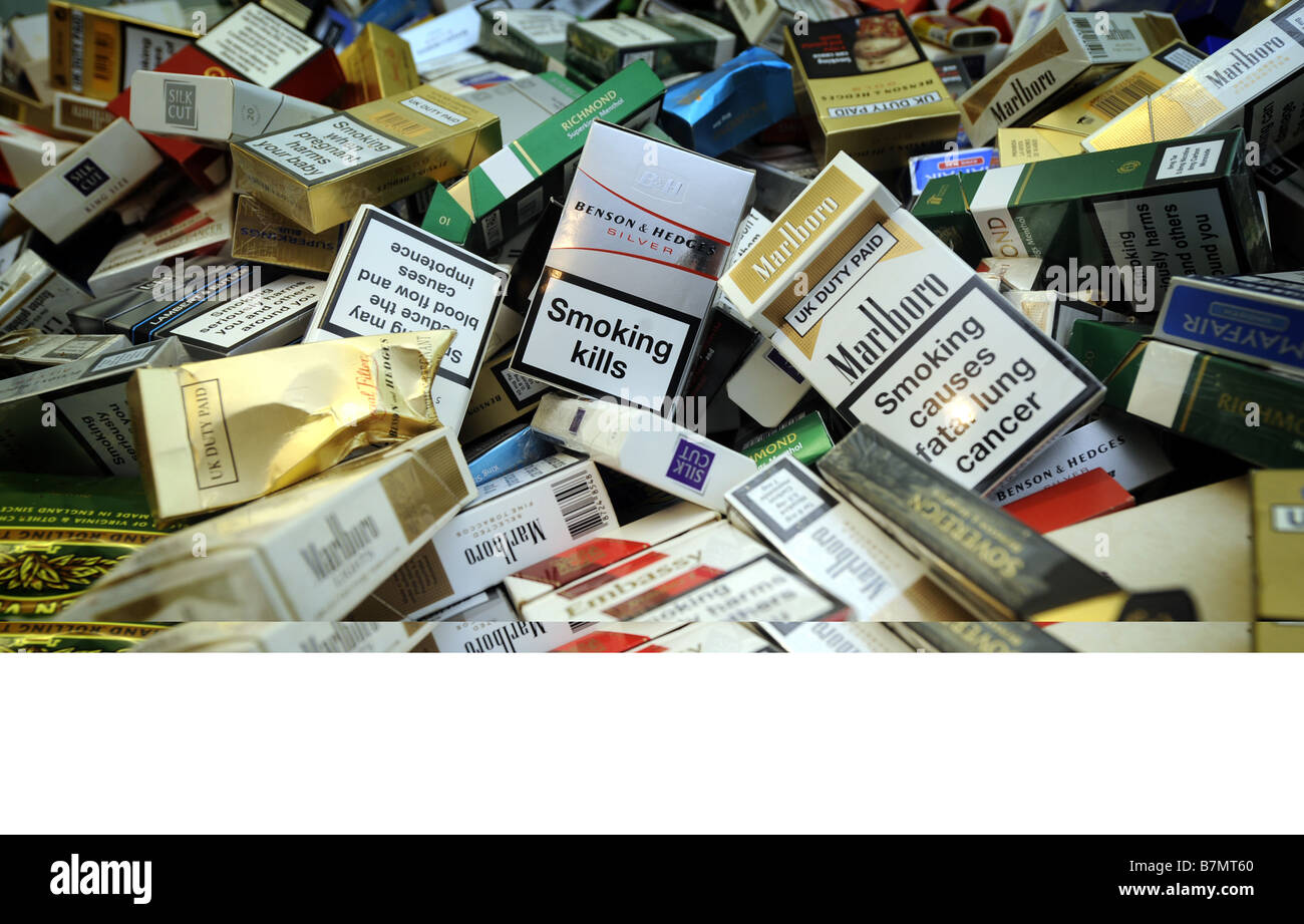PILES OF USED CIGARETTE PACKETS PACK PACKS RE SMOKERS SMOKING HEALTH - Stock Image
