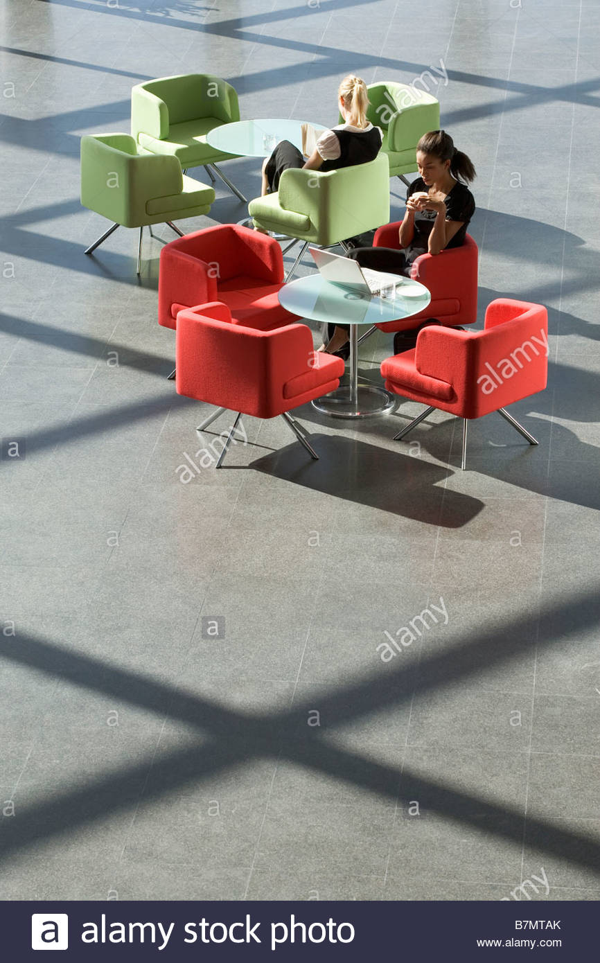 Two businesswomen sitting at tables in an office building - Stock Image