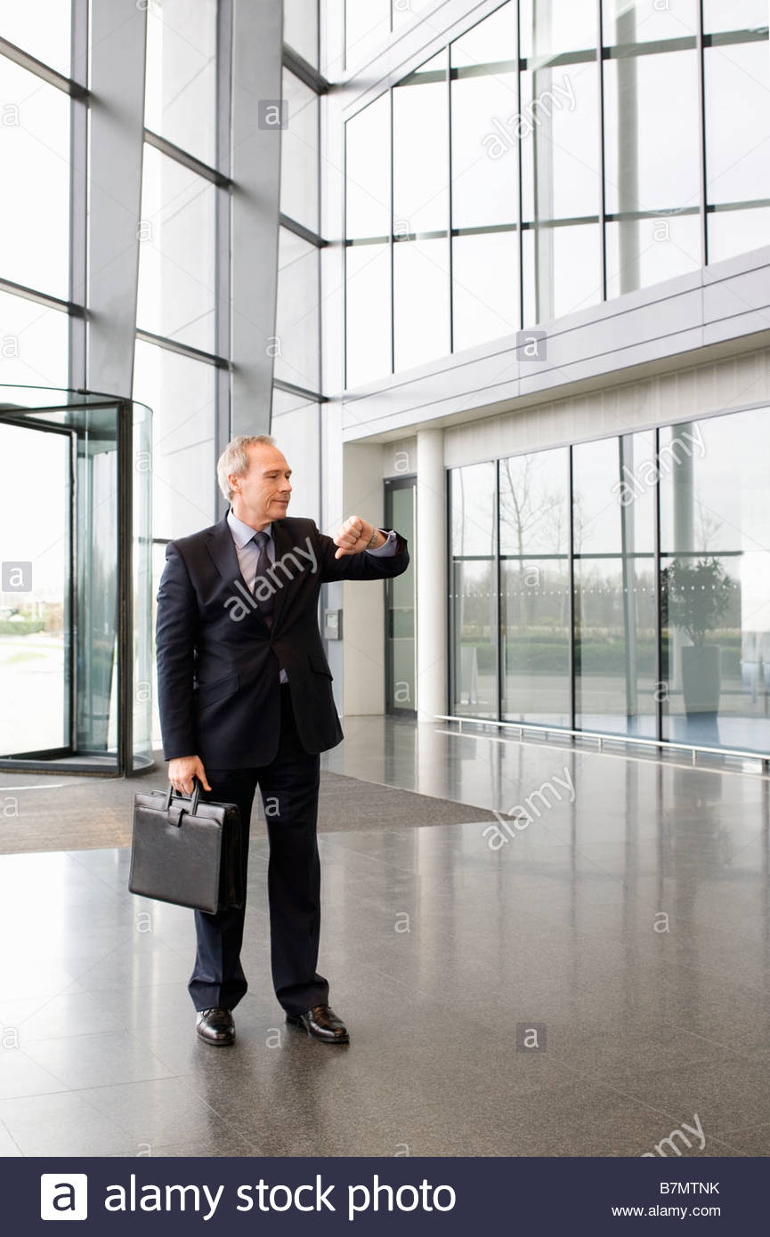 A mature businessman waiting in the lobby of a modern office building, checking his watch - Stock Image