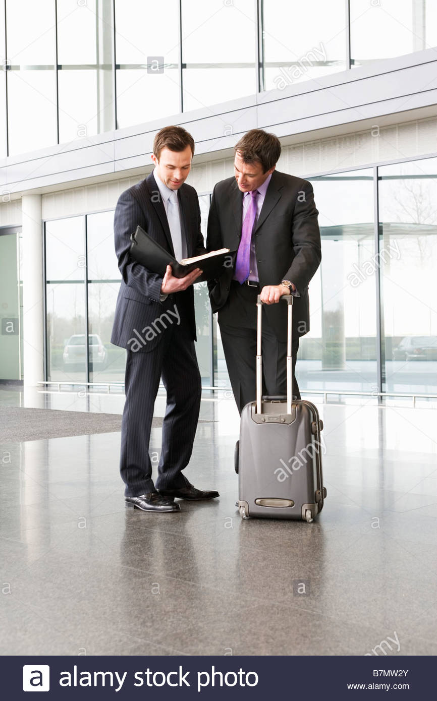 Two businessmen discussing business in the foyer of office building - Stock Image