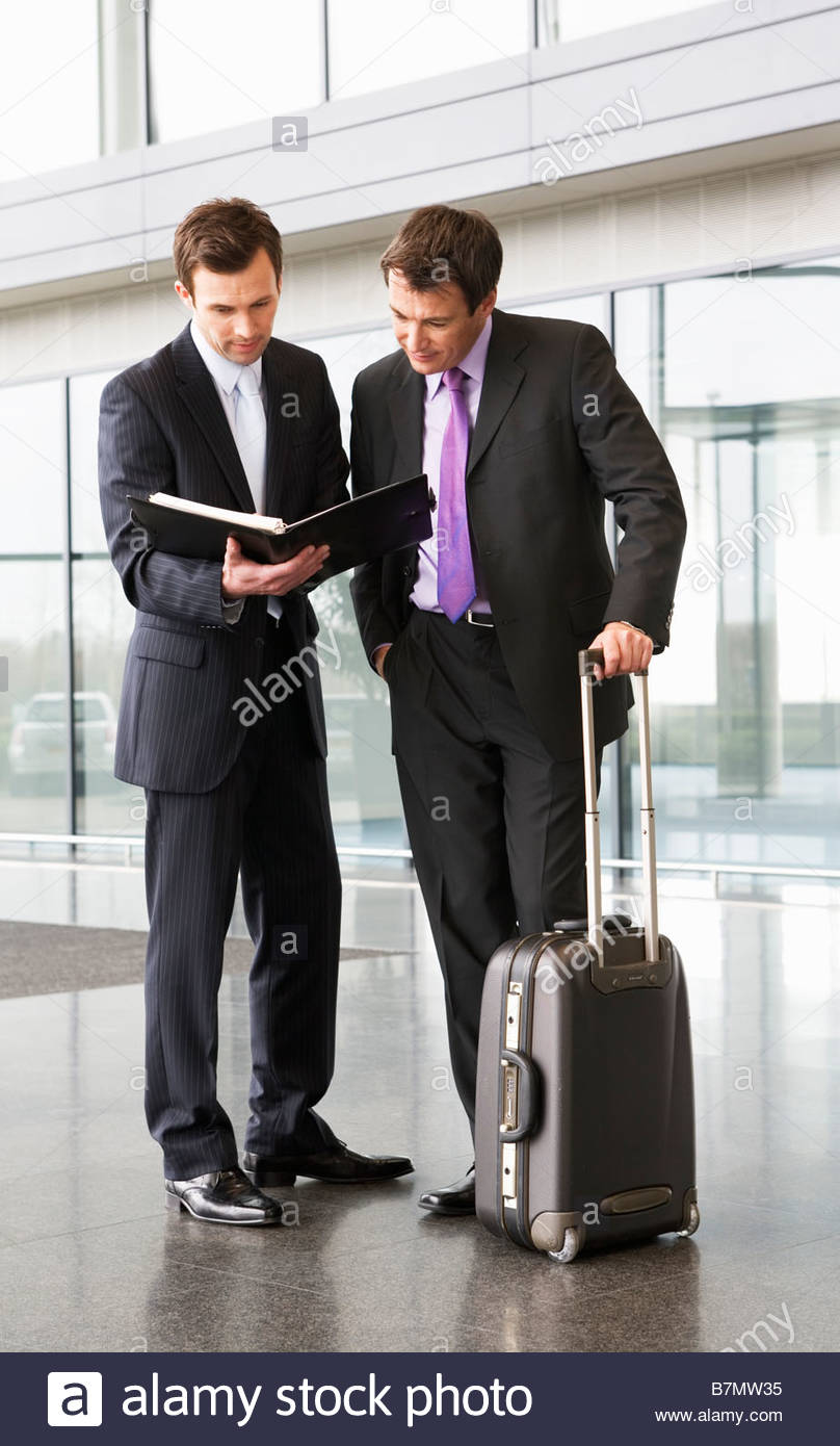 Two businessmen discussing papers in the foyer of an office building - Stock Image