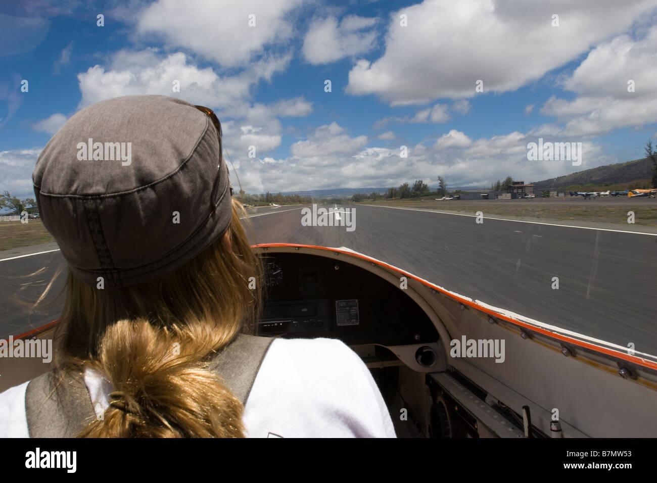 Female pilot landing glider airplane on runway at Dillingham Airfield in Oahu Hawaii - Stock Image