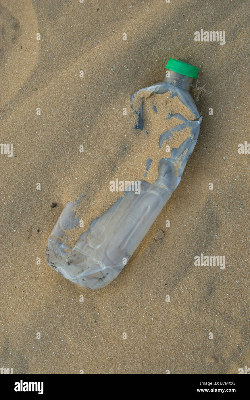 An empty smashed plastic water bottle in a sandy beach Stock Photo