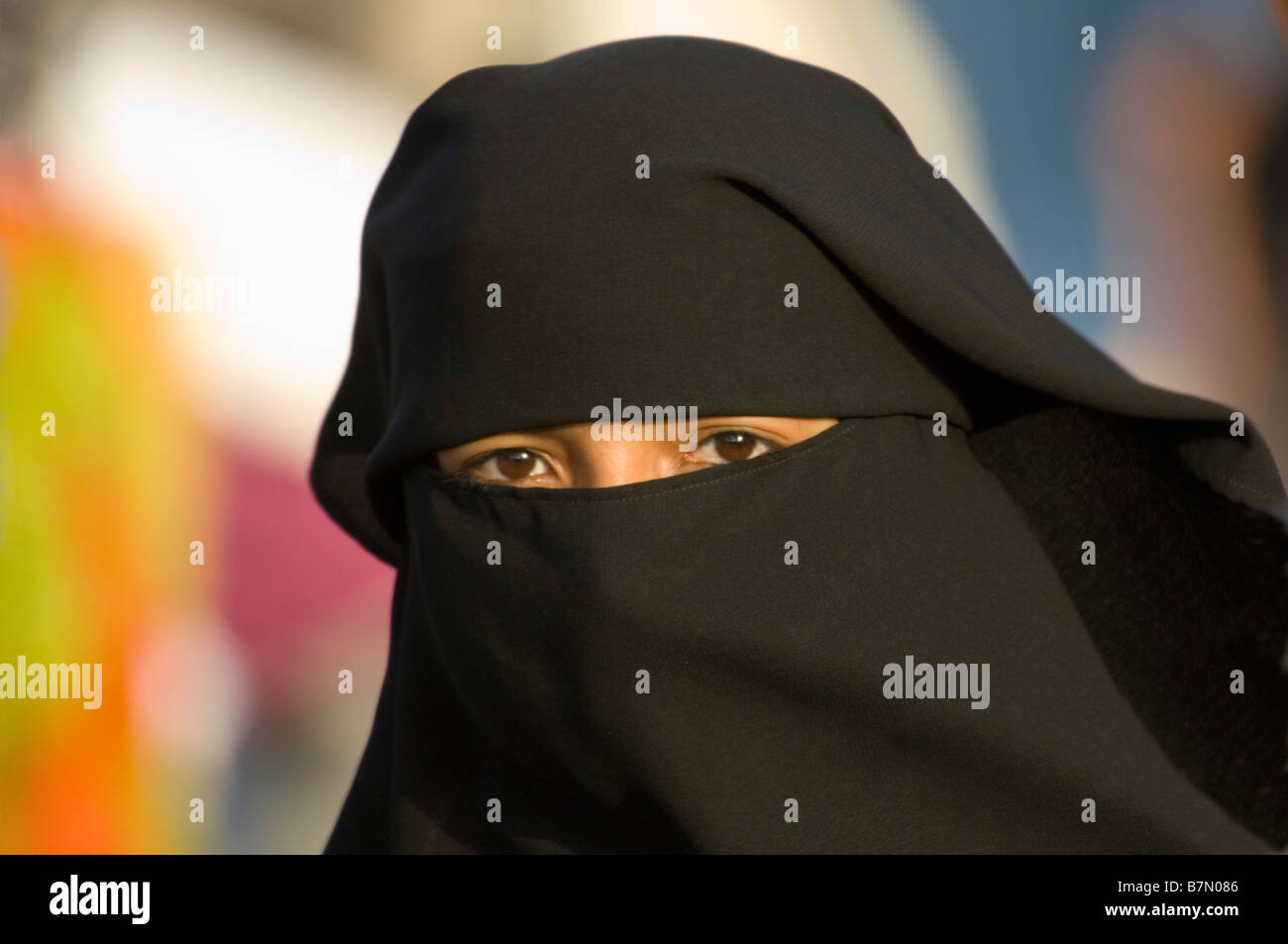 Young local Muslim lady wearing a black burka completely covering her face except the eyes. - Stock Image