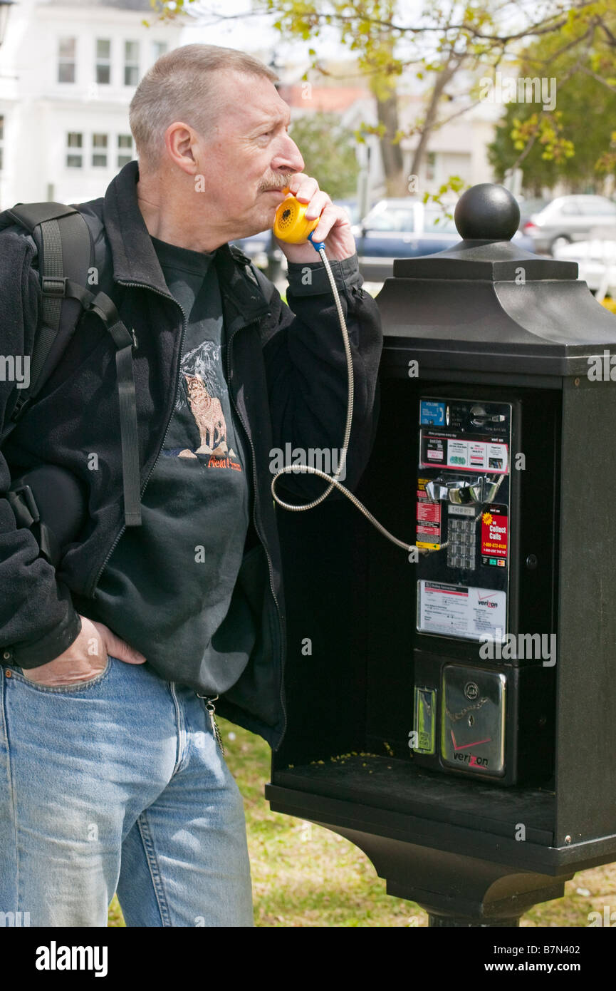 A man talking on a pay phone. - Stock Image
