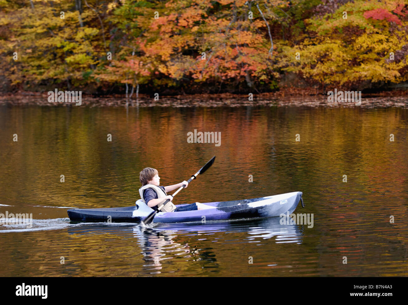Boy Paddling Kayak on Forested Lake in Autumn at Mount Saint Francis in Floyd County Indiana - Stock Image