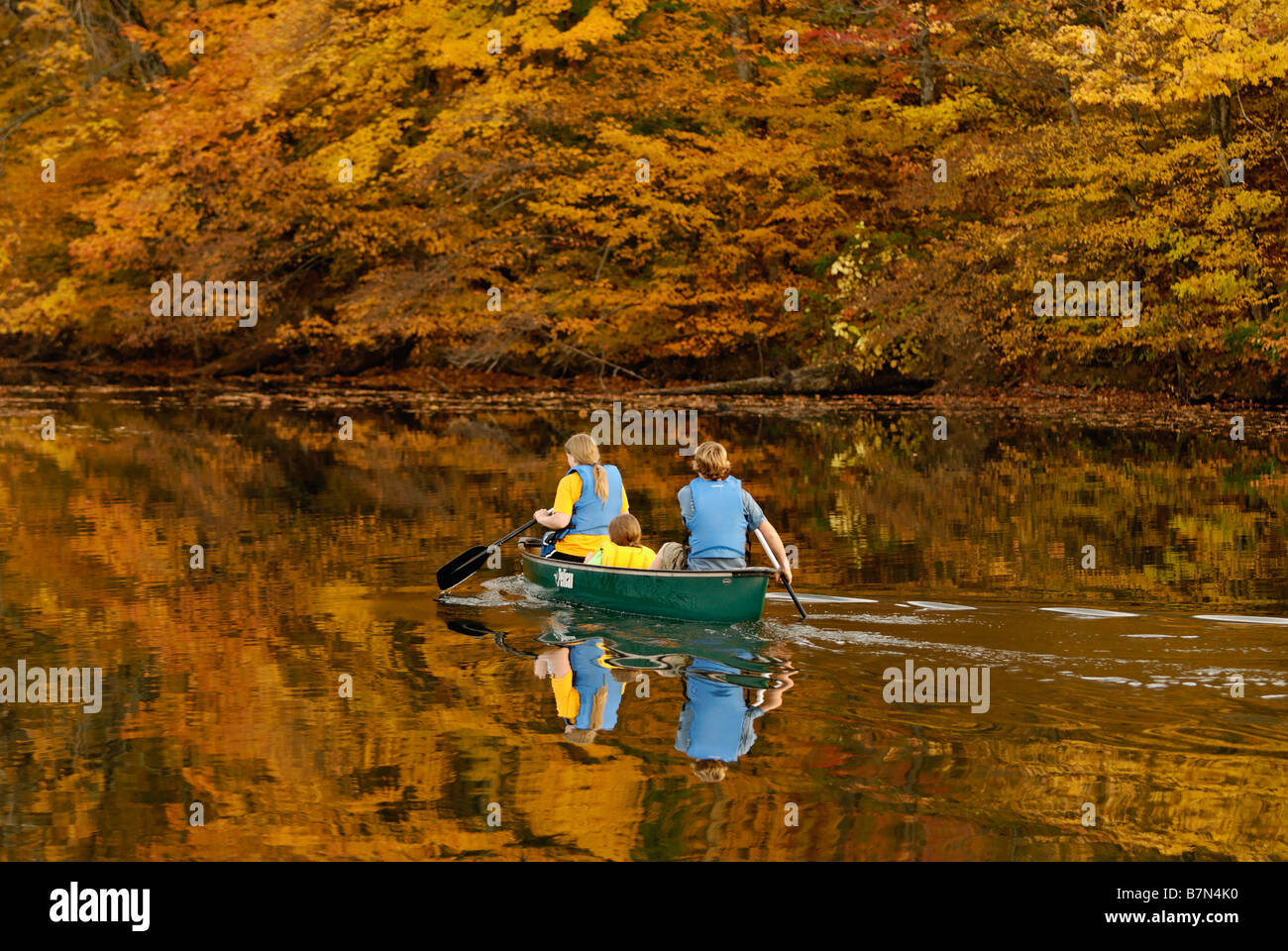 Three Teenagers in Canoe on Forested Lake in Autumn at Mount Saint Francis in Floyd County Indiana - Stock Image