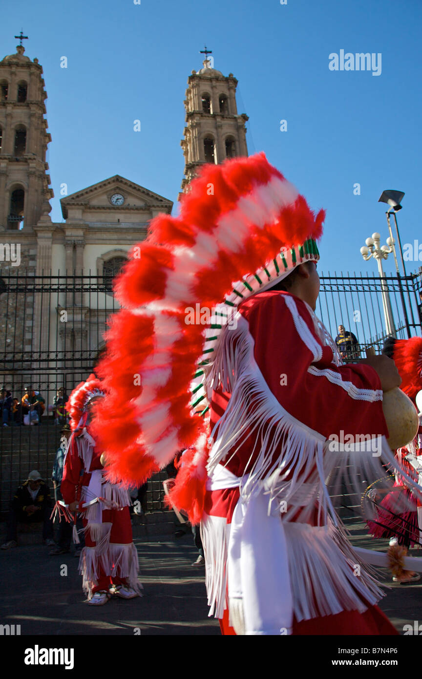 Children dressed in native indian costumes perform a traditional dance for the Virgin Mary outside the Ciudad Juarez - Stock Image