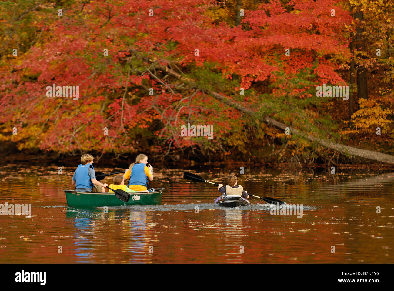 Teenagers in Canoe and Kayak on Forested Lake in Autumn at Mount Saint Francis in Floyd County Indiana - Stock Image