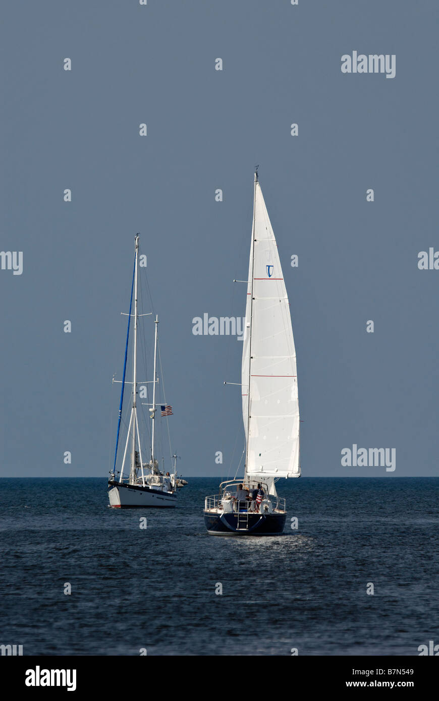 One Sailboat Motoring into the Macatawa River while another Sails out onto Lake Michigan in Ottawa County Michigan - Stock Image