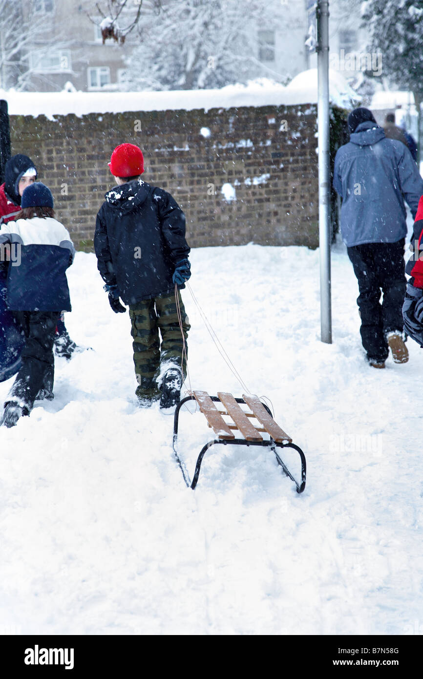 Back view of a young boy wearing a red hat pulling a sledge behind him. - Stock Image
