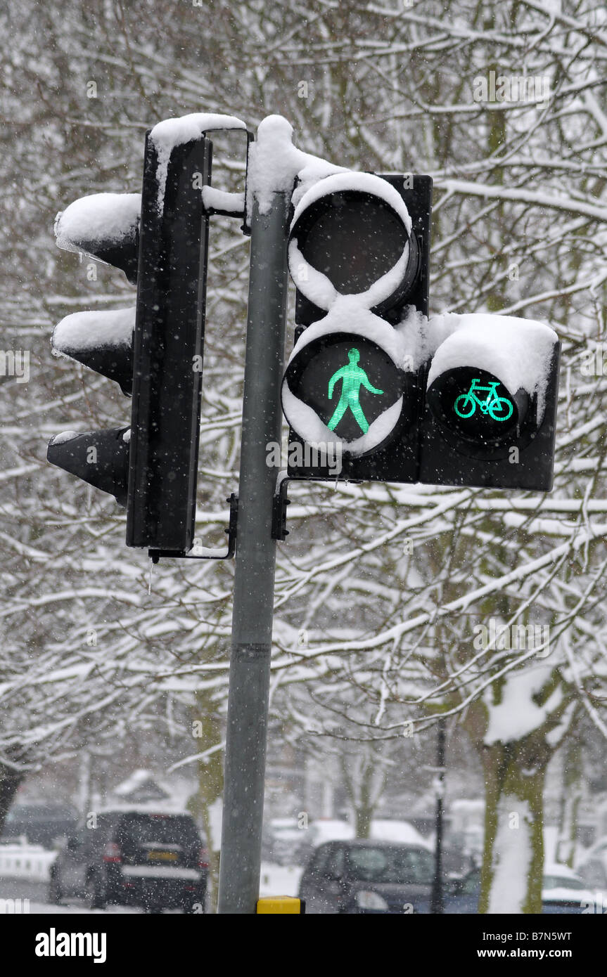 Traffic lights in the snow showing walk symbol - Stock Image