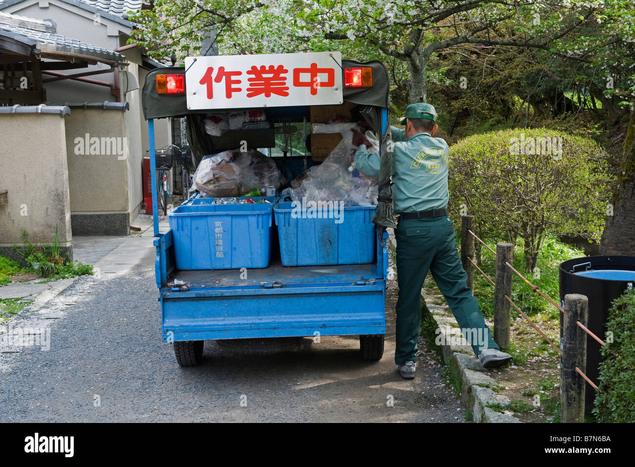 Kyoto, Japan. Collecting refuse underneath cherry blossom in spring - Stock Image