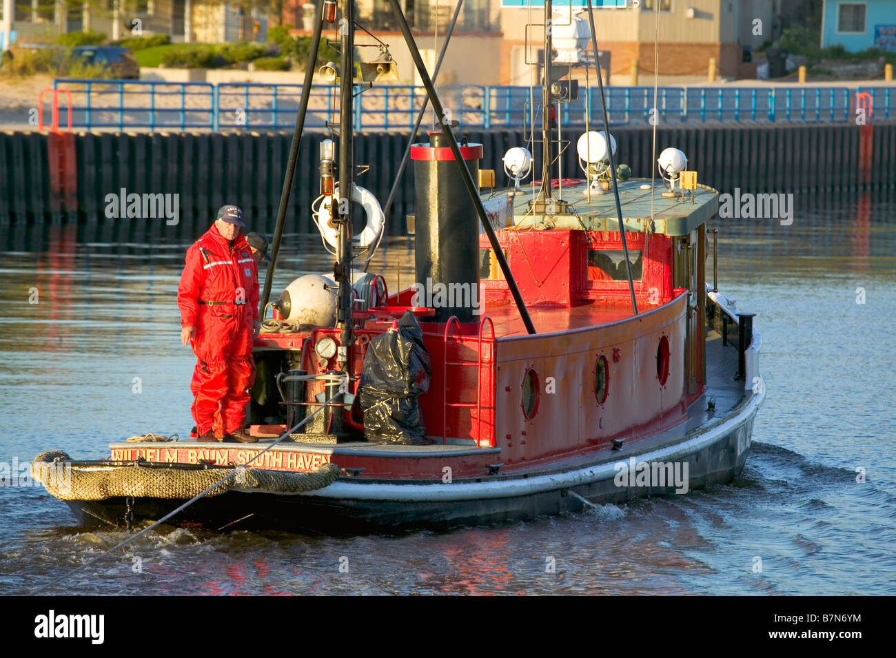 The historic tug Wilhelm Baum tows a stranded boat into South Haven Michigan - Stock Image