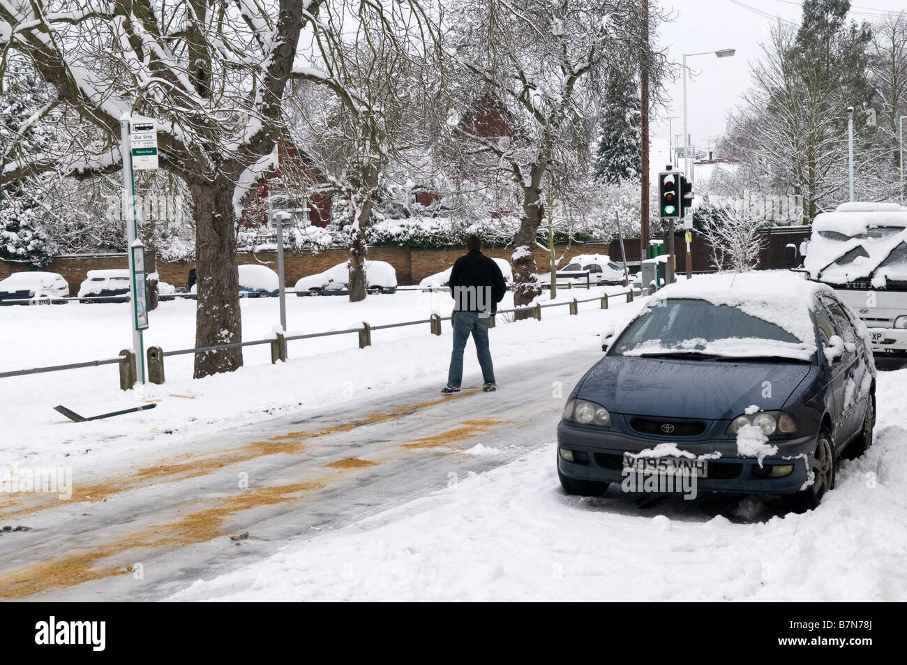 Volunteer helping to grit an icy, slippery road, in Weybridge, Surrey - Stock Image