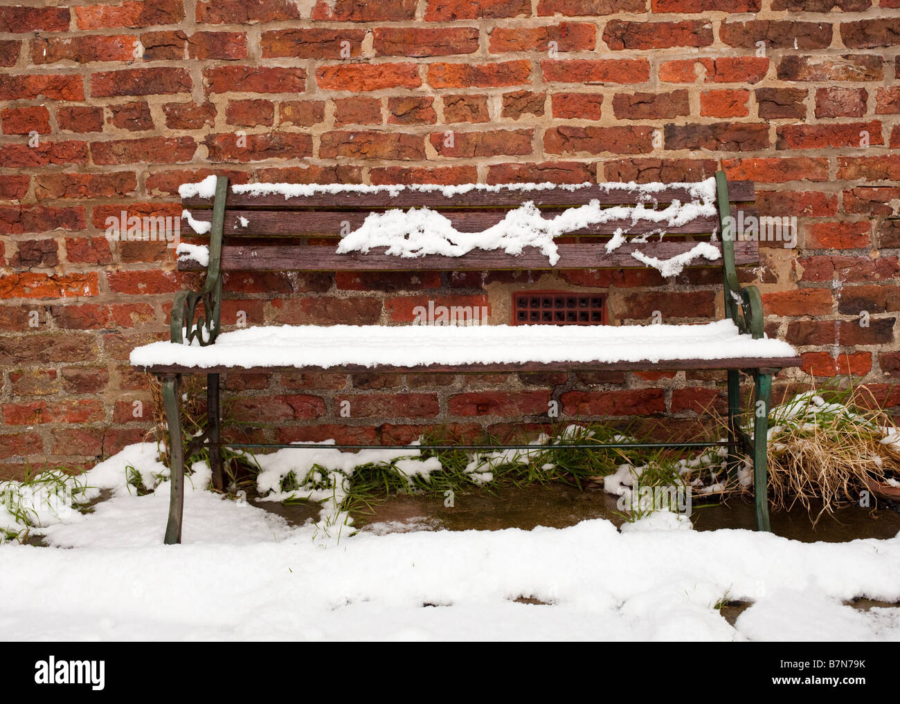 Old garden seat bench covered in snow in an English garden in winter - Stock Image
