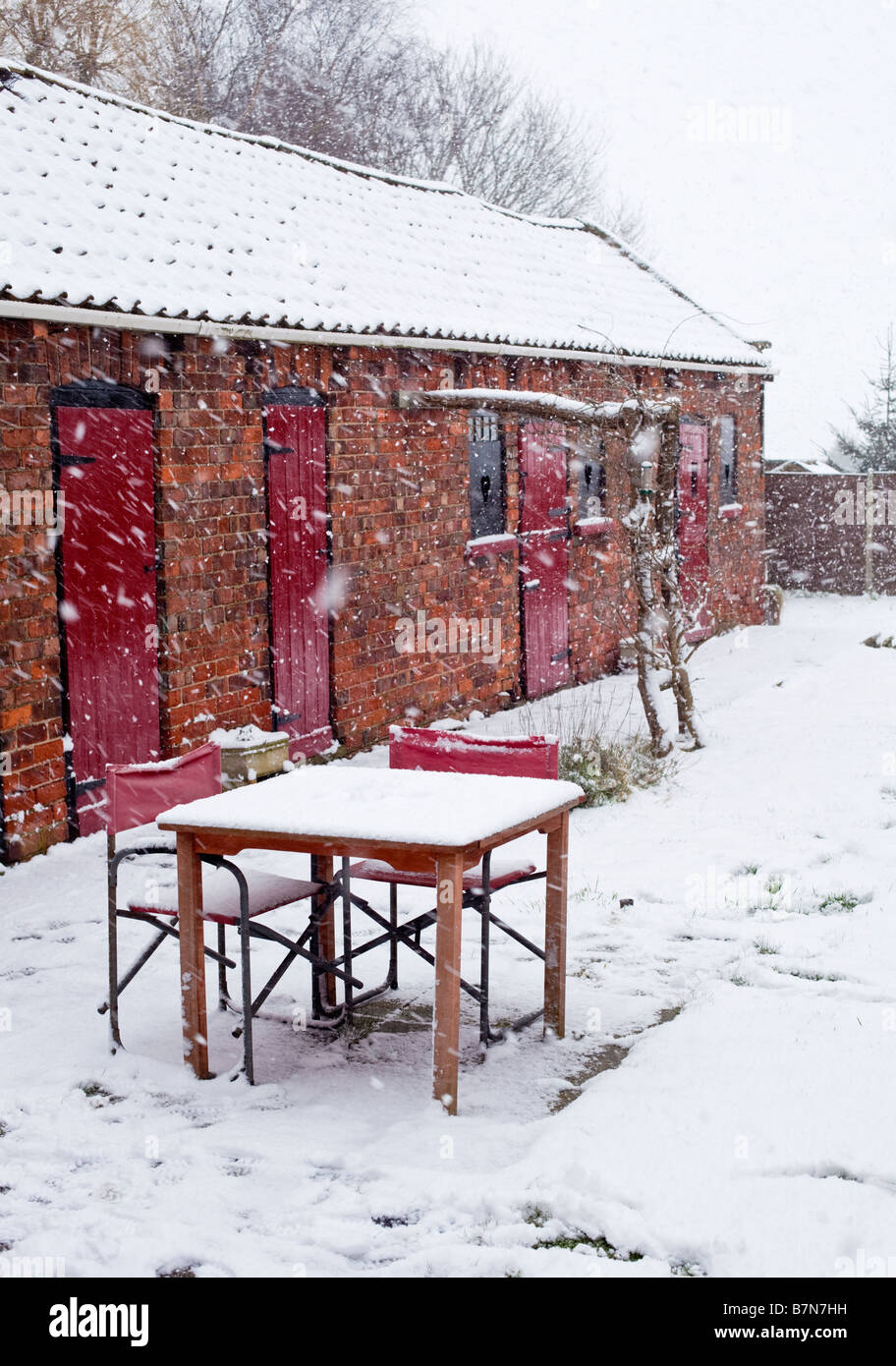 Garden table and chairs covered in fresh winter snow - Stock Image