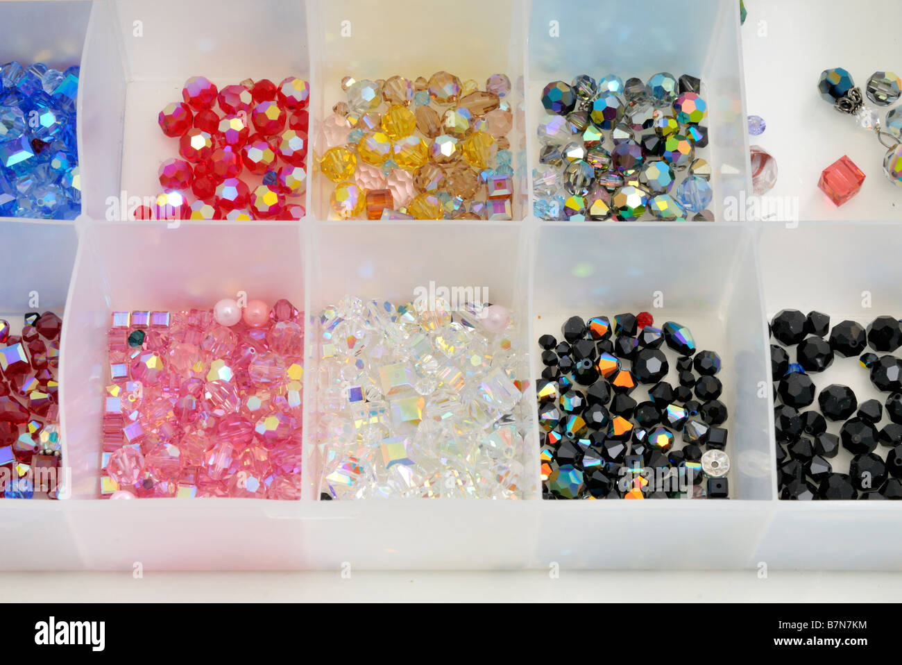 A partitioned plastic container full of Swarovski crystal beads for jewelry-making. USA. - Stock Image
