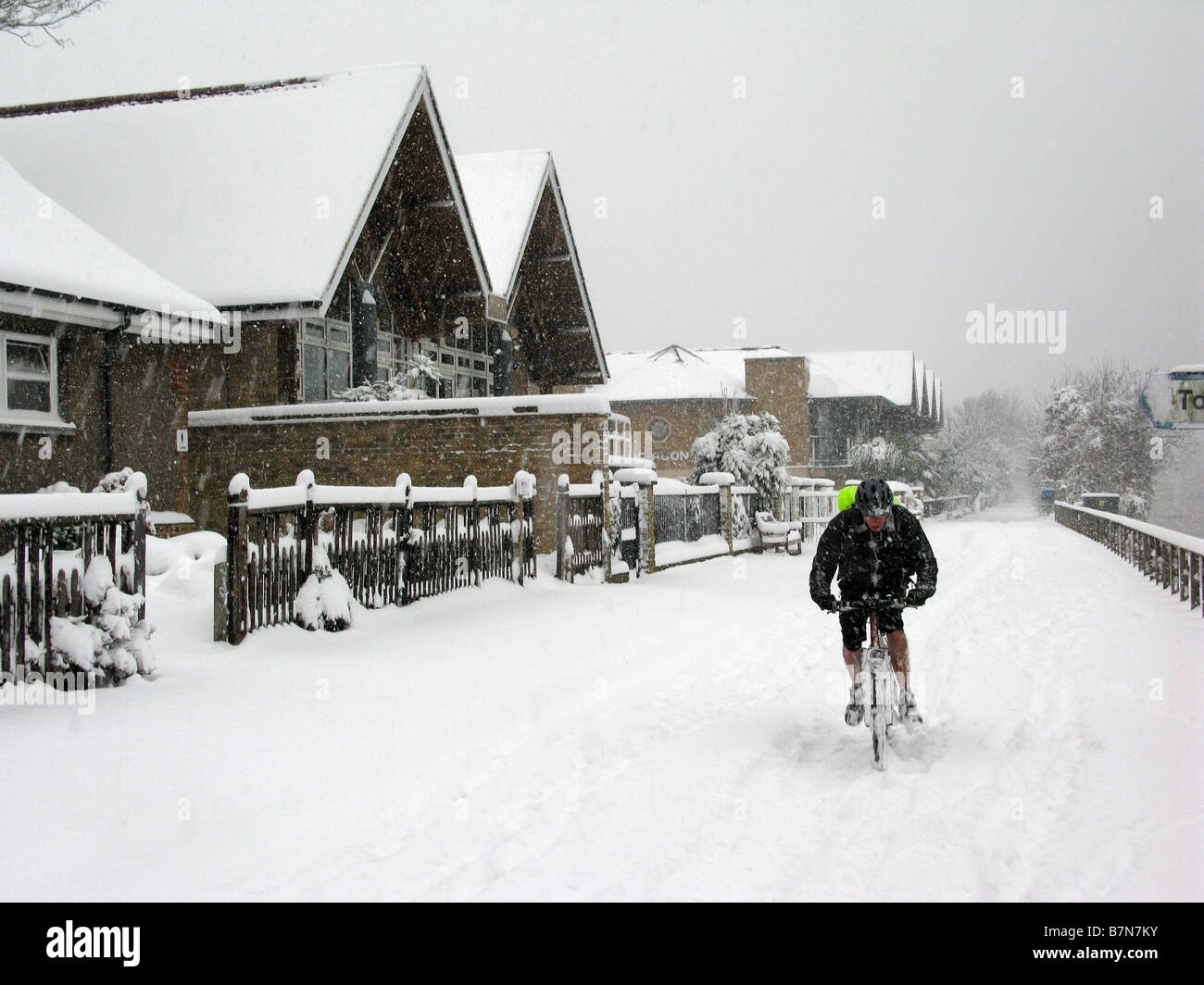 Man struggles to cycle through snow on the Thames towpath by Molesey Lock near Hampton Court, East Molesey, Surrey, - Stock Image