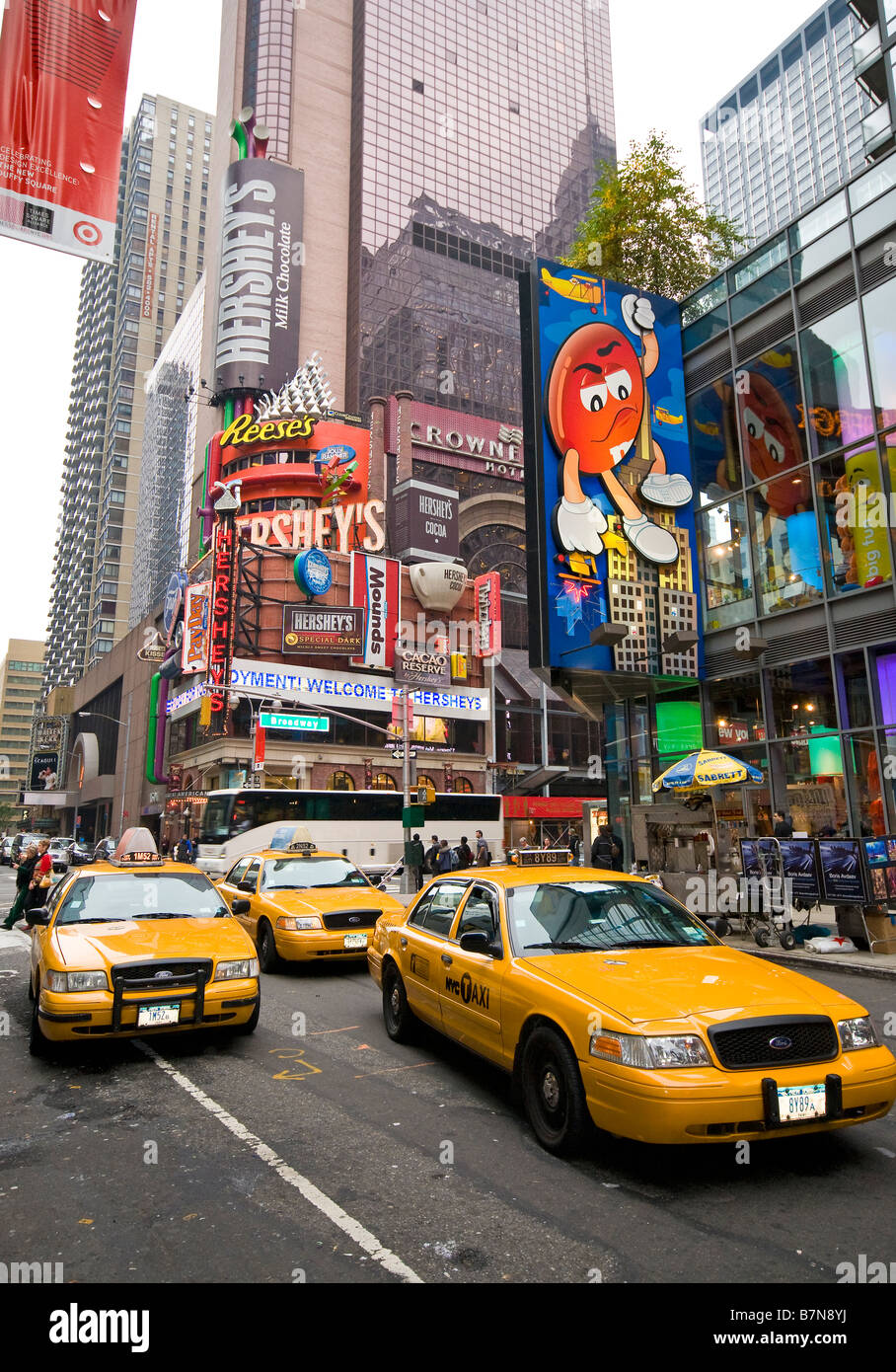 Yellow taxi cabs driving by the M&M's store, New York, USA - Stock Image