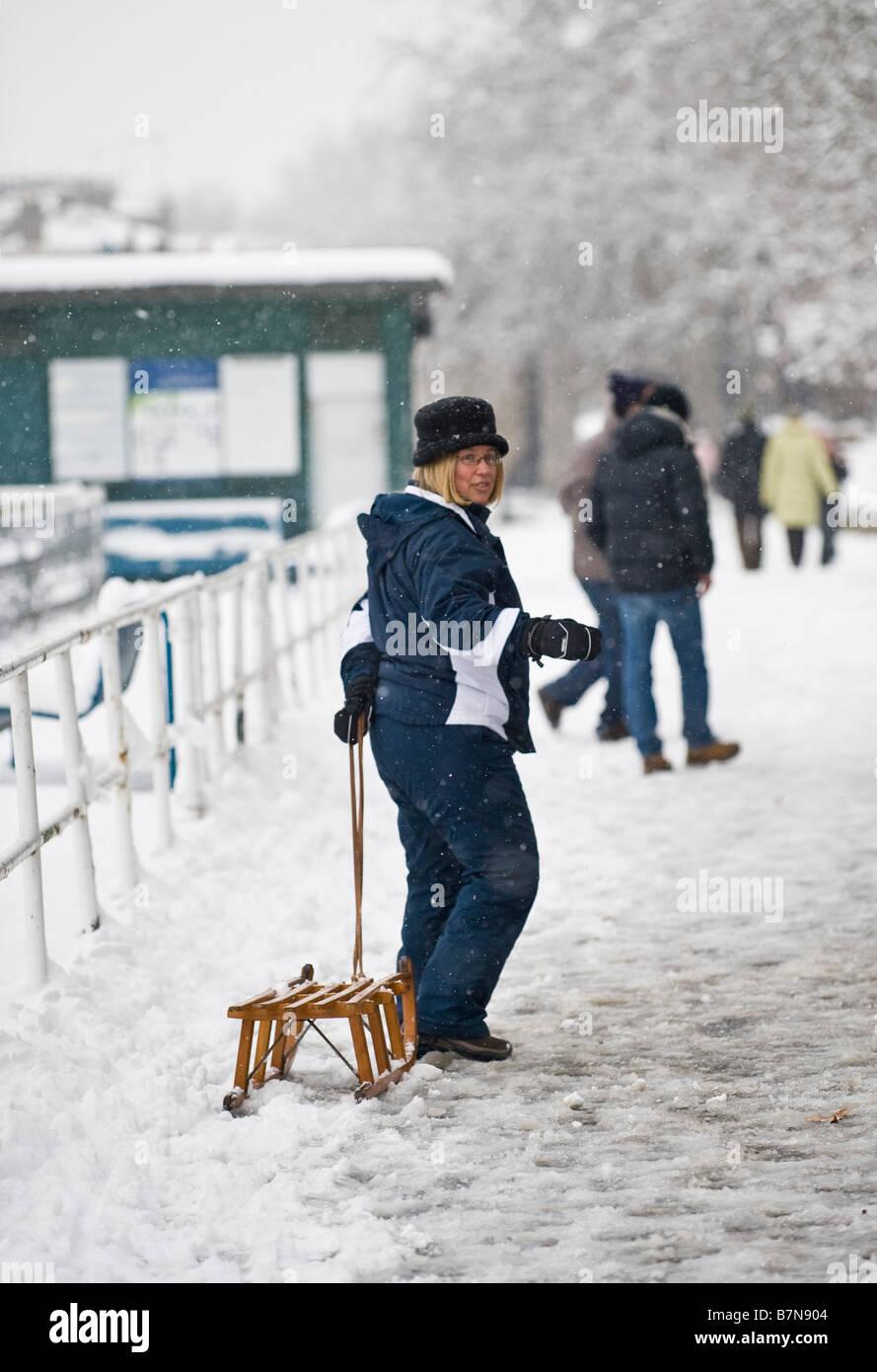 Woman pulling a wooden sledge, Richmond, London, UK - Stock Image