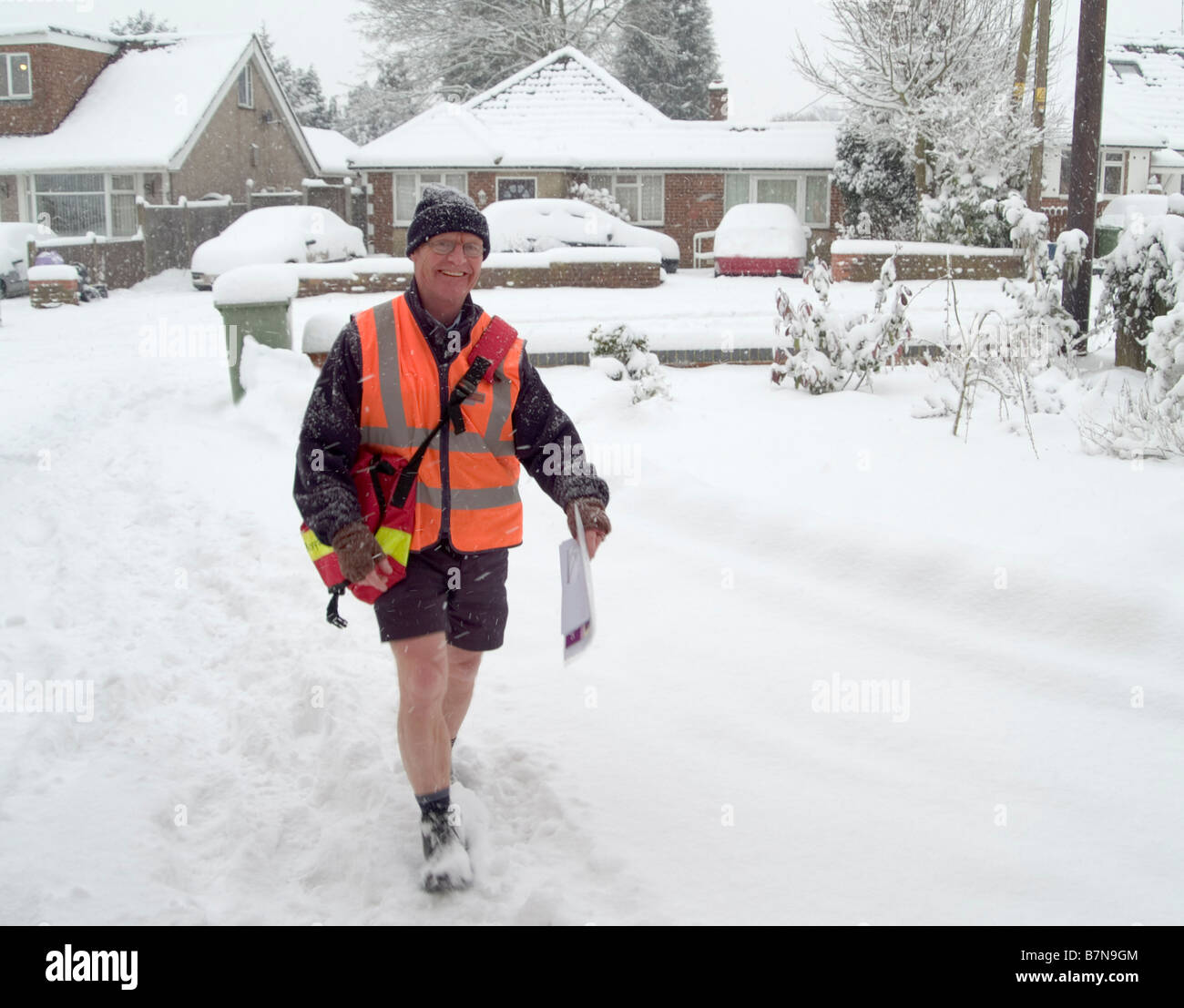 Cheery Postman wearing shorts during a snow storm. Biggin Hill, Bromley, Westerham, Kent England, UK. - Stock Image