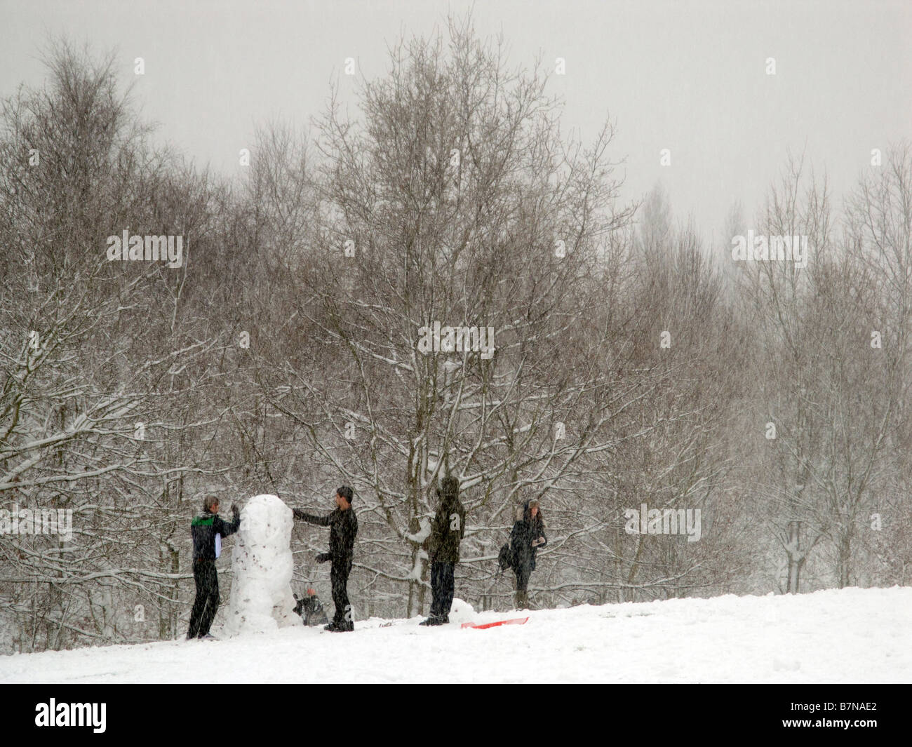 Youths building a snowman. - Stock Image