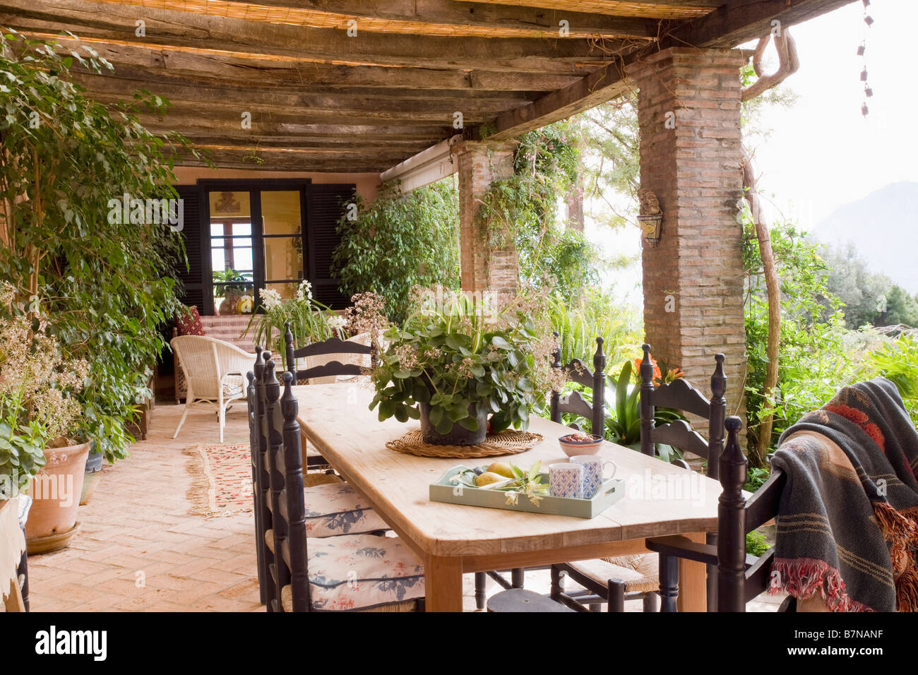 Wooden Table And Carved Chairs On Veranda Of Spanish Villa