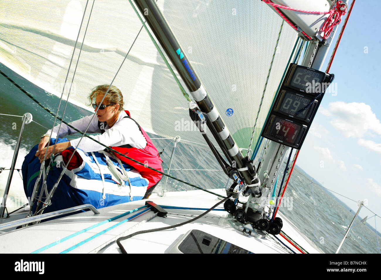 Female sailor stowing a sail on a Yacht in the Solent, UK. - Stock Image
