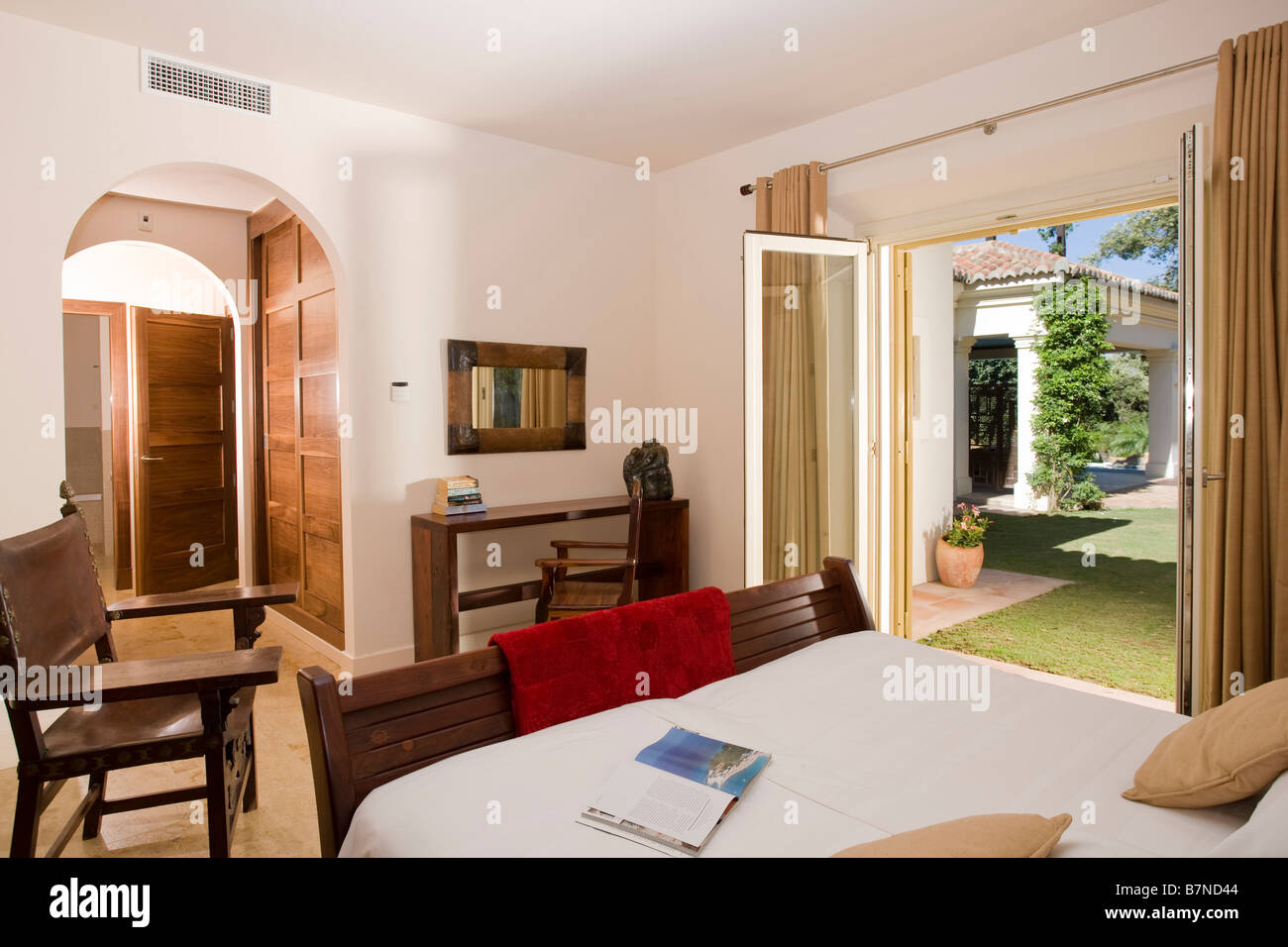 Simple Furniture In Modern Bedroom In Spanish Holiday Apartment With Patio  Doors To The Garden