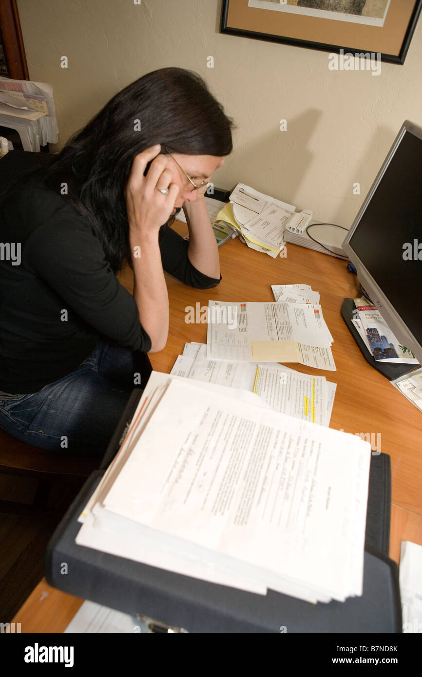 woman talking on cell phone at home at desk in home office surrounded by bills and paperwork - Stock Image