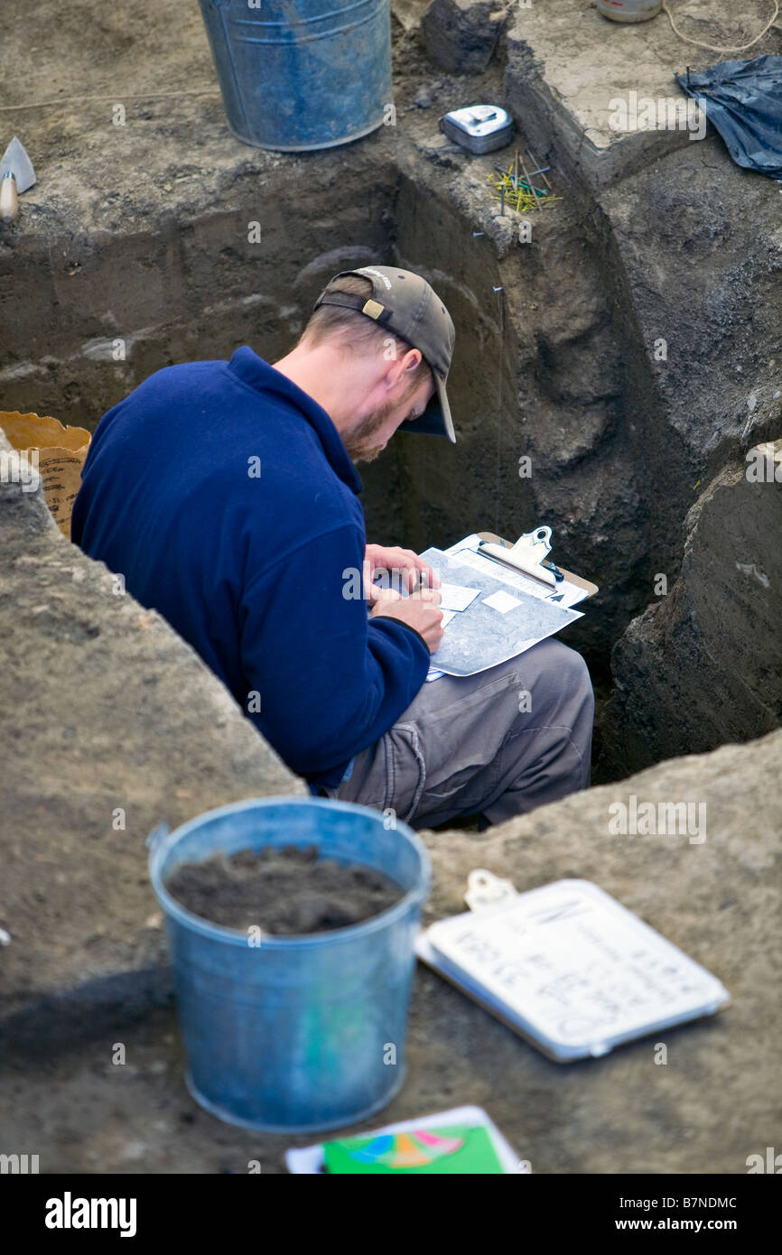 Archeologist recording information at an Archeology dig site. - Stock Image