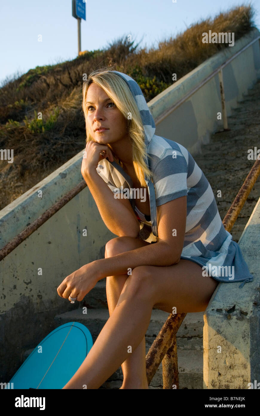 A young female surfer girl watches the surf Malibu California USA - Stock Image