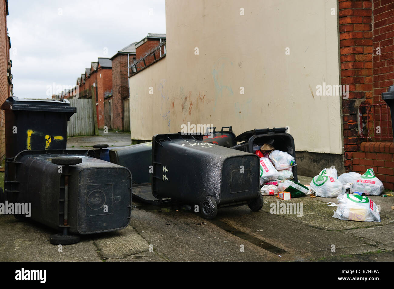 Household rubbish bins/trash cans lie toppled over on street with contents strewn over pavement/sidewalk/footpath Stock Photo